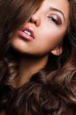 Beautiful young woman with long curly hairs — Stok fotoğraf
