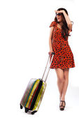 Full length of casual woman standing with travel suitcase - isolated on white background — Stock Photo