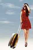 Full length of casual woman standing with travel suitcase - isol — 图库照片