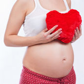 Pregnant mother showing her belly and holding a toy — Foto de Stock