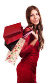 Fashion woman portrait isolated. White background. Happy girl hold shopping bag. Red dress. female beautiful model. — Zdjęcie stockowe