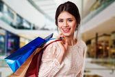 Mujer de belleza con bolsas de compras en el centro comercial. — Foto de Stock