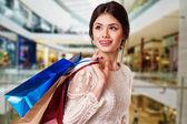 Frau schönheit mit einkaufstüten in einkaufszentrum. — Stockfoto