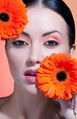 Portrait of beautiful woman with stylish make-up and bright flowers — Stock Photo