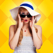 Portrait of a girl in a hat on a yellow background — Photo