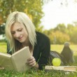 Stock Photo: Student girl reading on grass