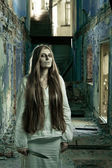 Zombie girl in abandoned building with knife — Stock Photo