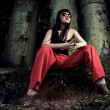 Stock Photo: Girl in red pants and glasses over industrial background