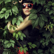 Stock Photo: Girl wearing red sun glasses over foliage background