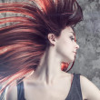 Girl with flying hair over grunge background — Stockfoto