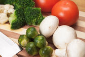 Fresh food ingredients and knife on the breadboard — Stock Photo