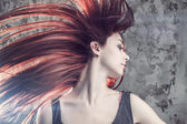 Flicka med flygande hår över grunge bakgrund — Stockfoto