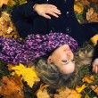 Foto Stock: Beautiful girl in scarf lying under autumn tree