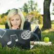Girl in park with laptop multimedia concept — Stock Photo