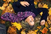 Beautiful girl in scarf lying under autumn tree — Stock Photo