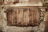 Wall of an abandoned house with boarded up window — Stockfoto