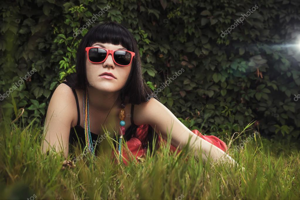 Beautiful girl wearing red sun glasses over foliage background — Stock Photo #13054095