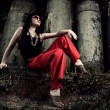 Girl in red pants and glasses sitting over industrial background — Stock Photo #13660602