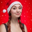 Young girl in Santa Claus hat over red snowy background — Stock Photo #13660739