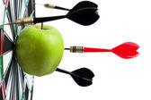 Dart hit green apple in the target center — Stock Photo