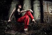 赤いズボンと眼鏡産業の背景の上に座っている女の子 — ストック写真