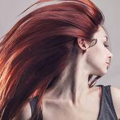Chica con pelo de vuelo sobre fondo gris — Foto de Stock