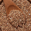 Brown wooden bowl full of buckwheat close-up — Stock Photo