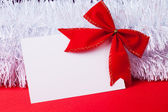 Blank christmas greeting card with red bow — Stock Photo