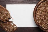 Buckwheat over brown wooden background and blank sheet of paper — Stock Photo
