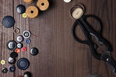 Threads buttons and needles on brown wooden table — Foto Stock