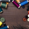 Threads buttons and needles on the brown wooden table — Stock Photo