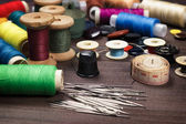 Needles buttons and threads on brown wooden table — Stock Photo