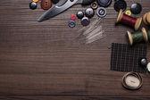 Naalden threads en knoppen op bruin houten tafel — Stockfoto