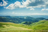 Verano montañas verde césped y azul cielo paisaje — Foto de Stock