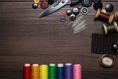 Buttons, needles and multicolored threads on wooden table — Stock Photo