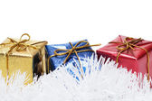 Colorful present boxes on tinsel over white background — Stock Photo