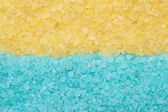 Blue and yellow aromatic bath salt background — Stock Photo