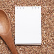 Buckwheat with brown wooden spoon and notepad — Stockfoto