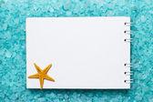 Notepad and starfish on bath salt background — Stock Photo