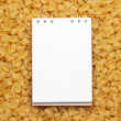 Blank notepad on uncooked macaroni background — Stockfoto