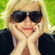 Young girl in sunglasses sitting on grass — Stock Photo #22319933