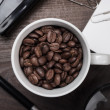 Cup of coffee beans on wooden table in the office — Stockfoto