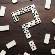 Domino pieces forming question mark on wooden table — Stockfoto
