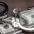 Handcuffs and one hundred dollars on the table — Stock Photo #23346460