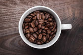 Cup of coffee beans on brown wooden background — Stock Photo