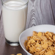 Glass of milk and bowl with cornflakes — Stockfoto