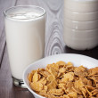 Glass of milk and bowl of cornflakes — Stock Photo