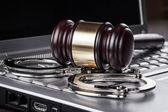 Handcuffs and judge gavel on computer concept — Stockfoto