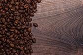 Granos de café en la mesa de madera marrón — Foto de Stock