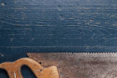 Old rusty saw on blue table — Stok fotoğraf